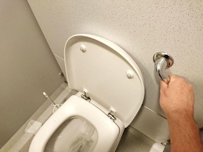 Cropped image of man flushing toilet