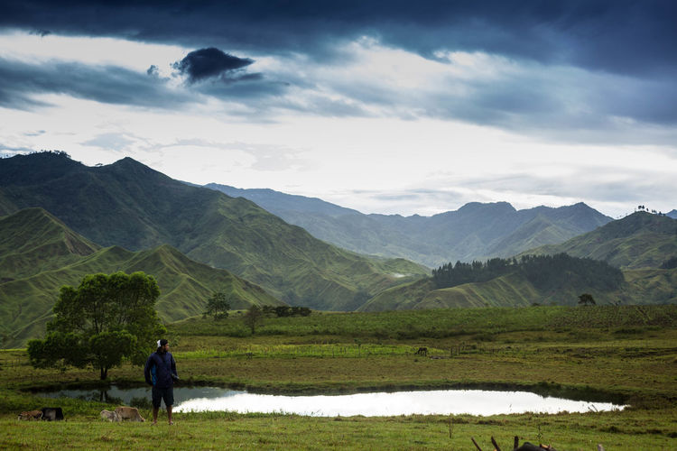 Young man standing on field against pond and mountains