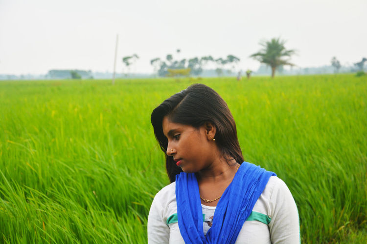 Teenage girl looking down while standing at field
