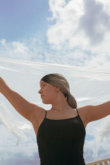 Woman standing with arms raised against sky