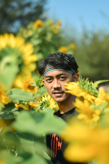 Portrait of young man against yellow flowering plants