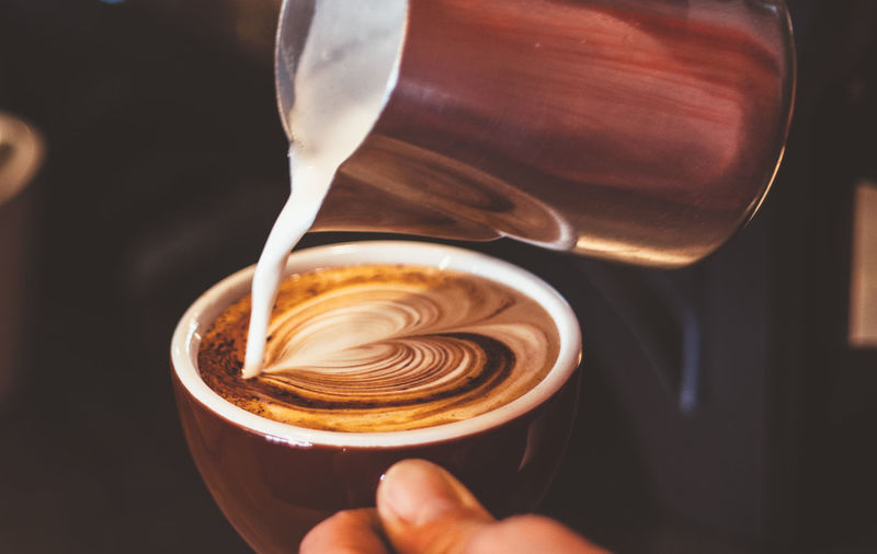 Cropped hand of person pouring milk in coffee cup
