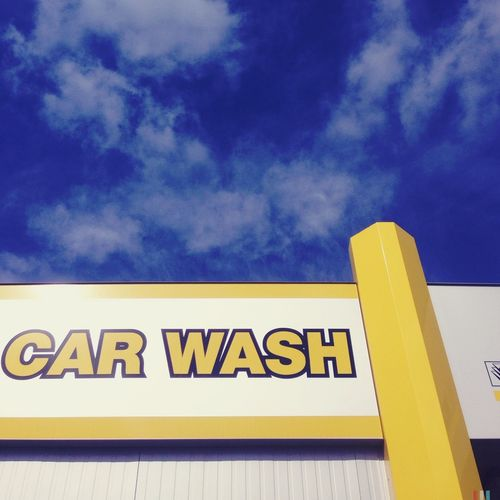 Low Angle View Of Sign On Car Wash Shop Against Sky