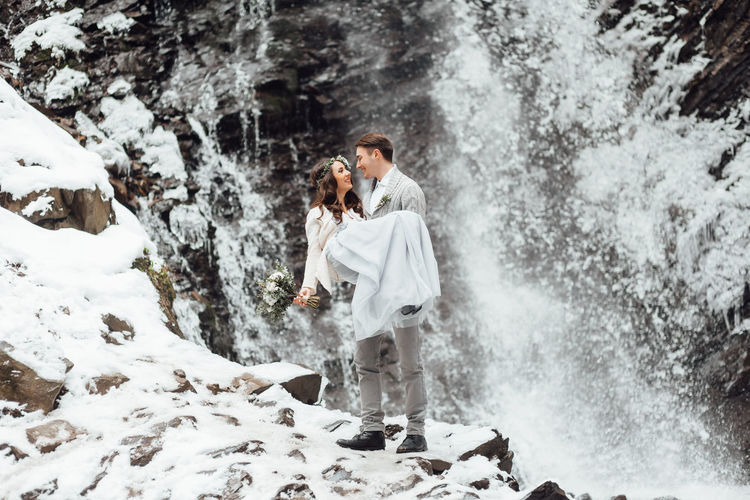 Panoramic view of young woman standing by waterfall