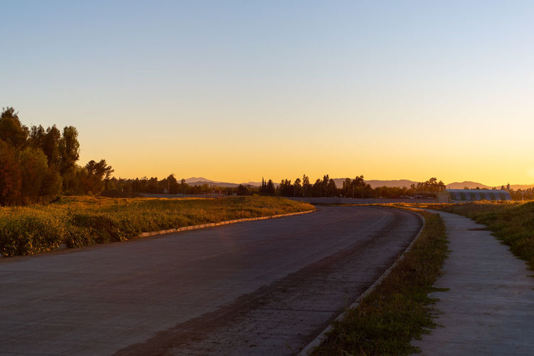 Sky Road Sunset Plant Direction The Way Forward Transportation Clear Sky Nature Tree No People Tranquil Scene Copy Space Tranquility City Landscape Beauty In Nature Scenics - Nature Outdoors Environment