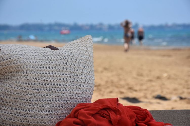 Close-Up Of Bag And Red Scarf Against Defocused People At Beach