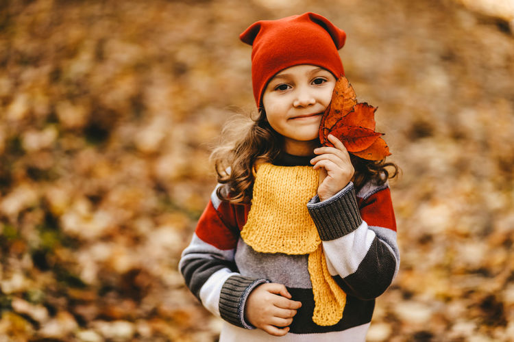 Portrait of a little girl a child in a warm hat walk holding an autumn leaf in fall forest outdoor