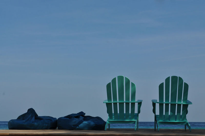 Adirondack Chairs With Bean Bags On Pier Against Sky