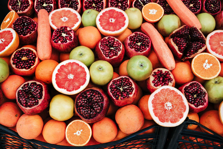 A variety of ripe fruit pomegranates, oranges, apples on the counter.