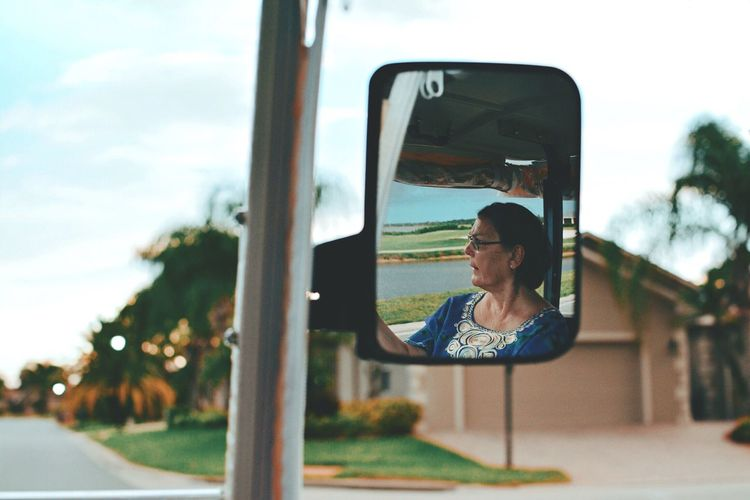 Woman reflecting on side-view mirror against sky