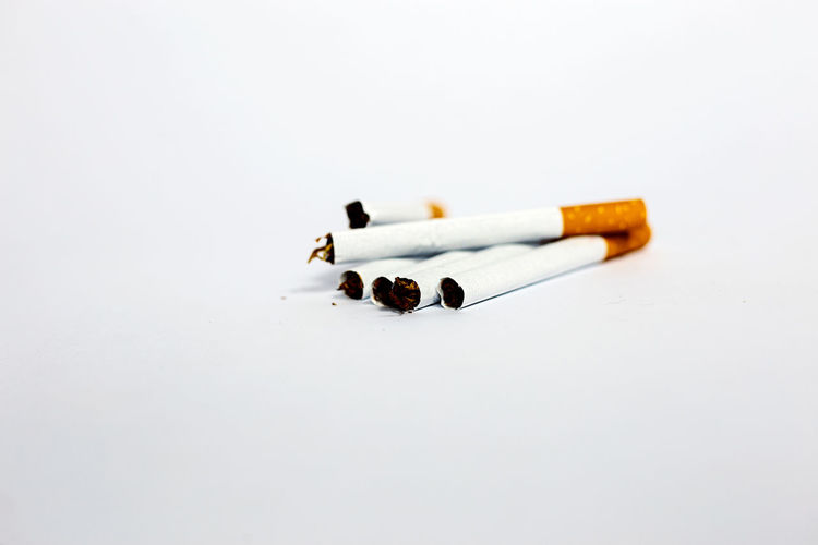 Close-up of cigarette smoking against white background