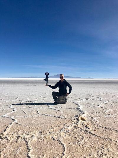 Digital composite image of woman holding man while kneeling on salt flat against blue sky