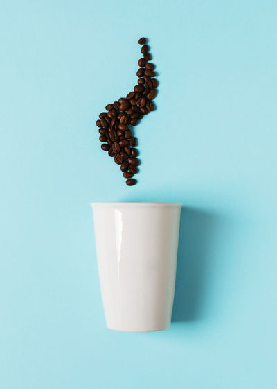 Close-up of coffee cup against blue background