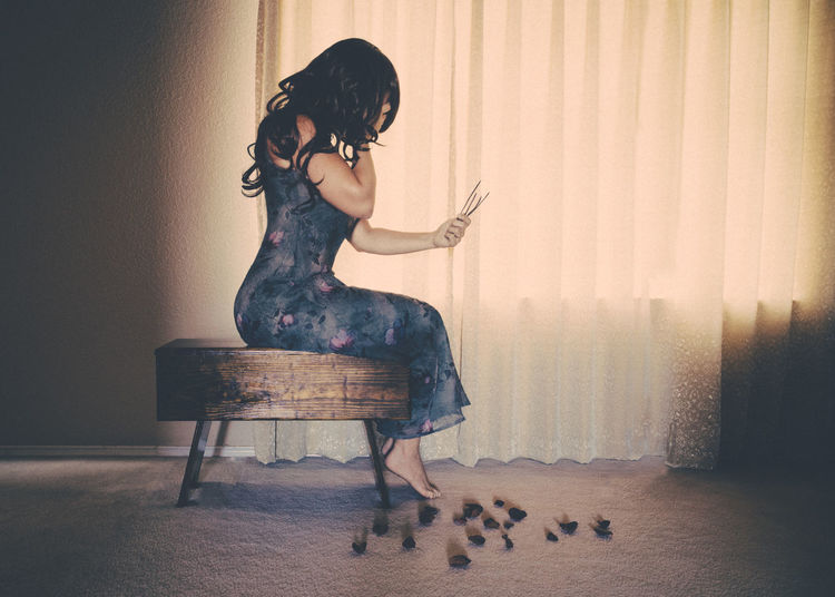 Bare Feet Bedroom Conceptual Copy Space Curtain Dress Emotional Emotions Face Covered Filtered Light Full Body Full Length Grief Hand On Face Long Hair Melancholy One Person Portrait Sad Sadness Scattered Petals Sitting Tragedy Window Light Woman