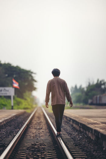 Man walk away on railroad with warm light. selective focus. traveler man on railroad. person