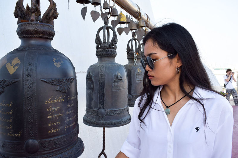 Close-up of young woman standing by bells against sky