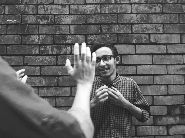 Cropped Hands Of Man With Male Friend Standing Against Brick Wall