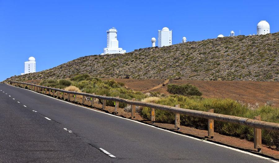 Road leading towards lighthouse against clear blue sky
