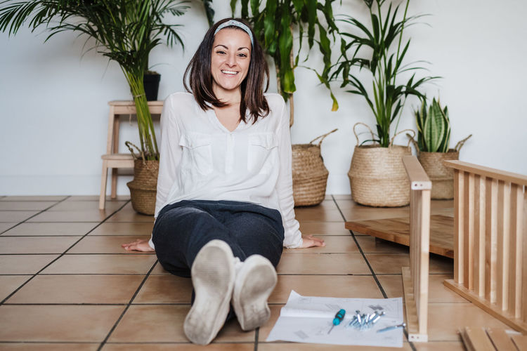 Portrait of smiling woman sitting on wooden floor at home