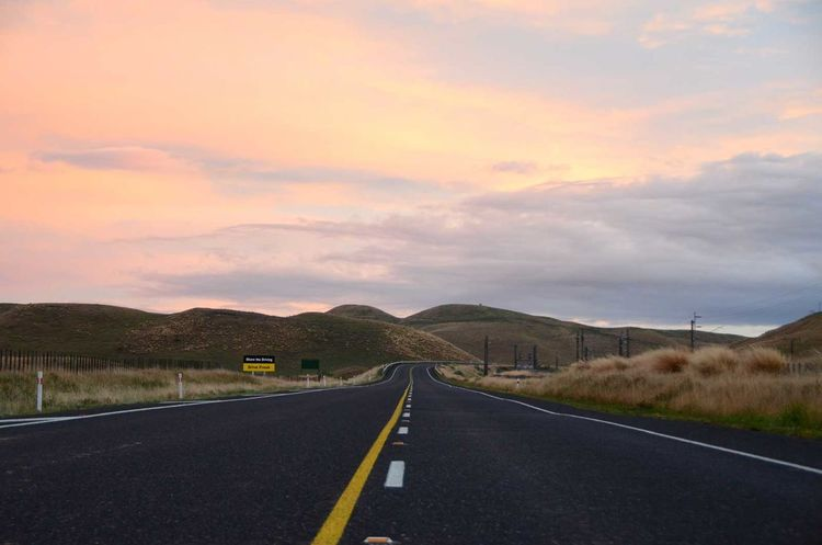 Cloud Cloud - Sky Country Road Countryside Day Diminishing Perspective Double Yellow Line Landscape Long Mountain Nature Non-urban Scene Orange Color Outdoors Road Road Marking Sky Solitude Surface Level The Way Forward Tranquil Scene Tranquility Transportation Vanishing Point Yellow Line
