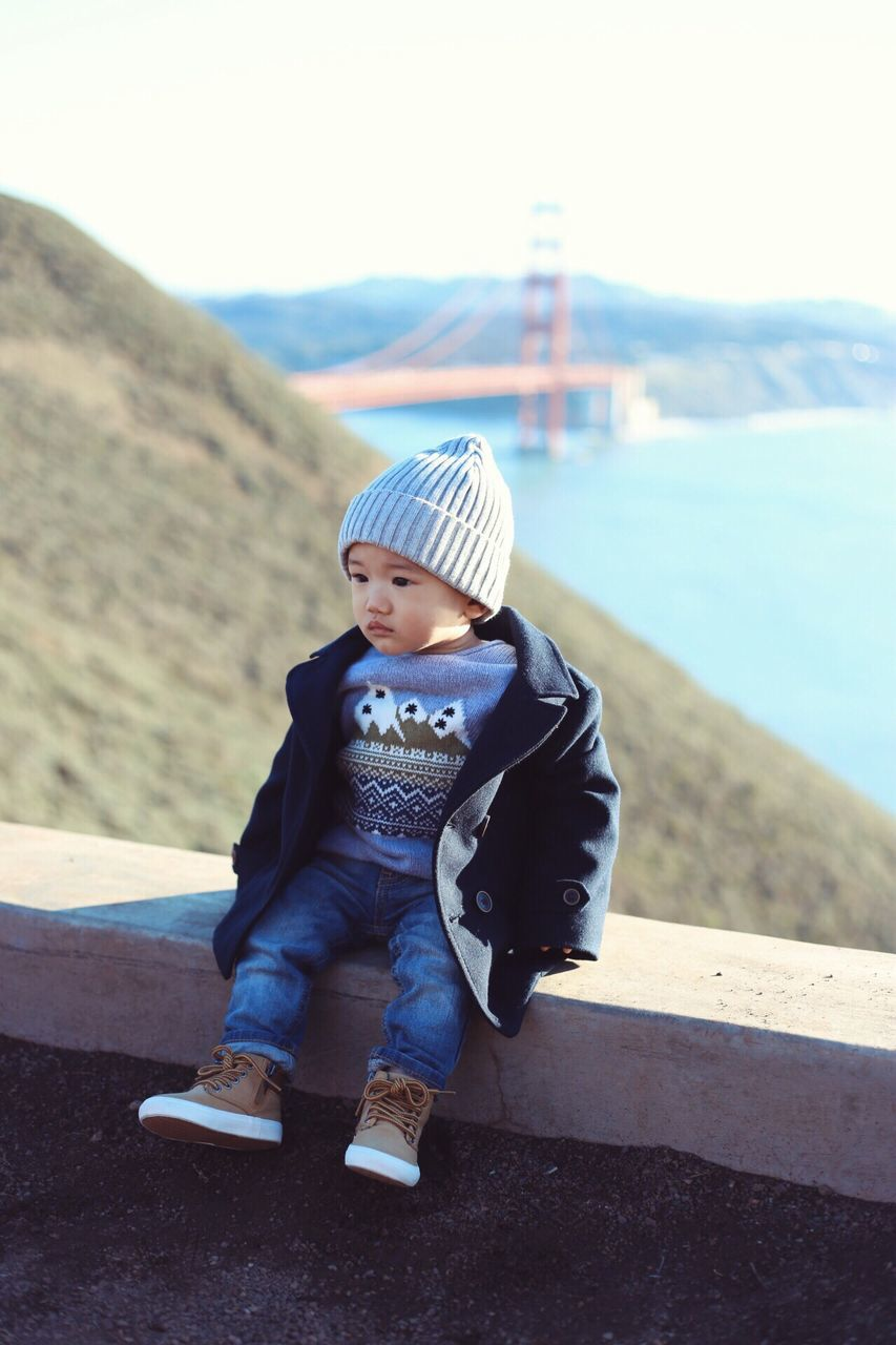 full length, real people, one person, childhood, day, casual clothing, knit hat, babyhood, outdoors, cap, lifestyles, boys, warm clothing, sky, nature, people