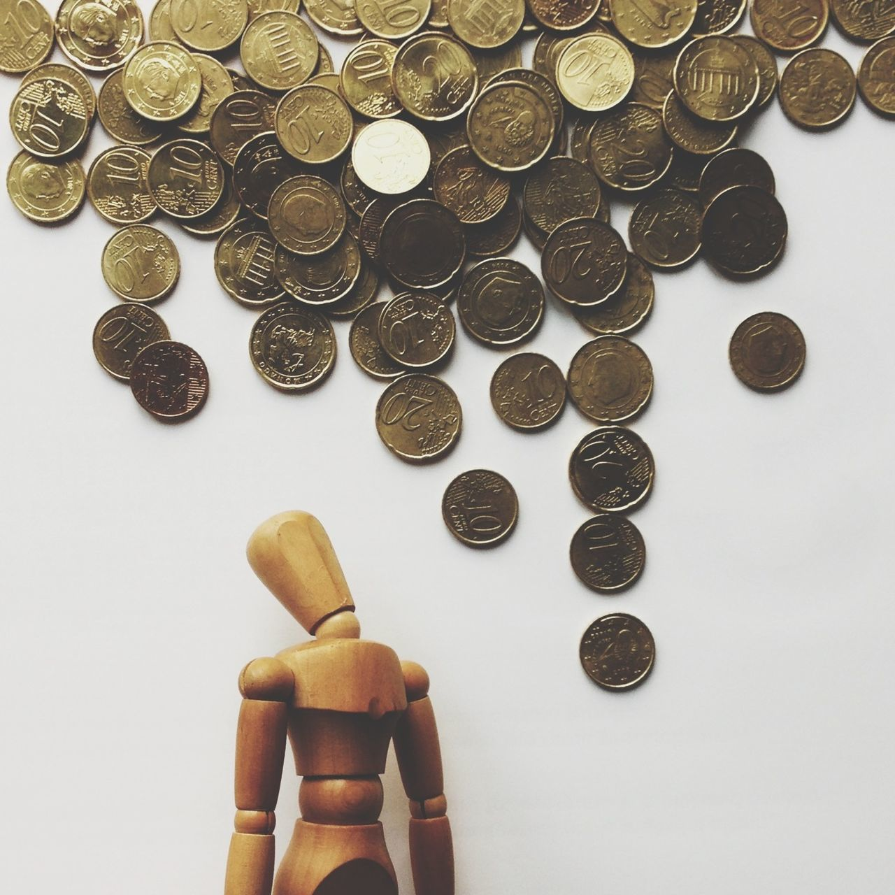 Euro coins with wooden figurine