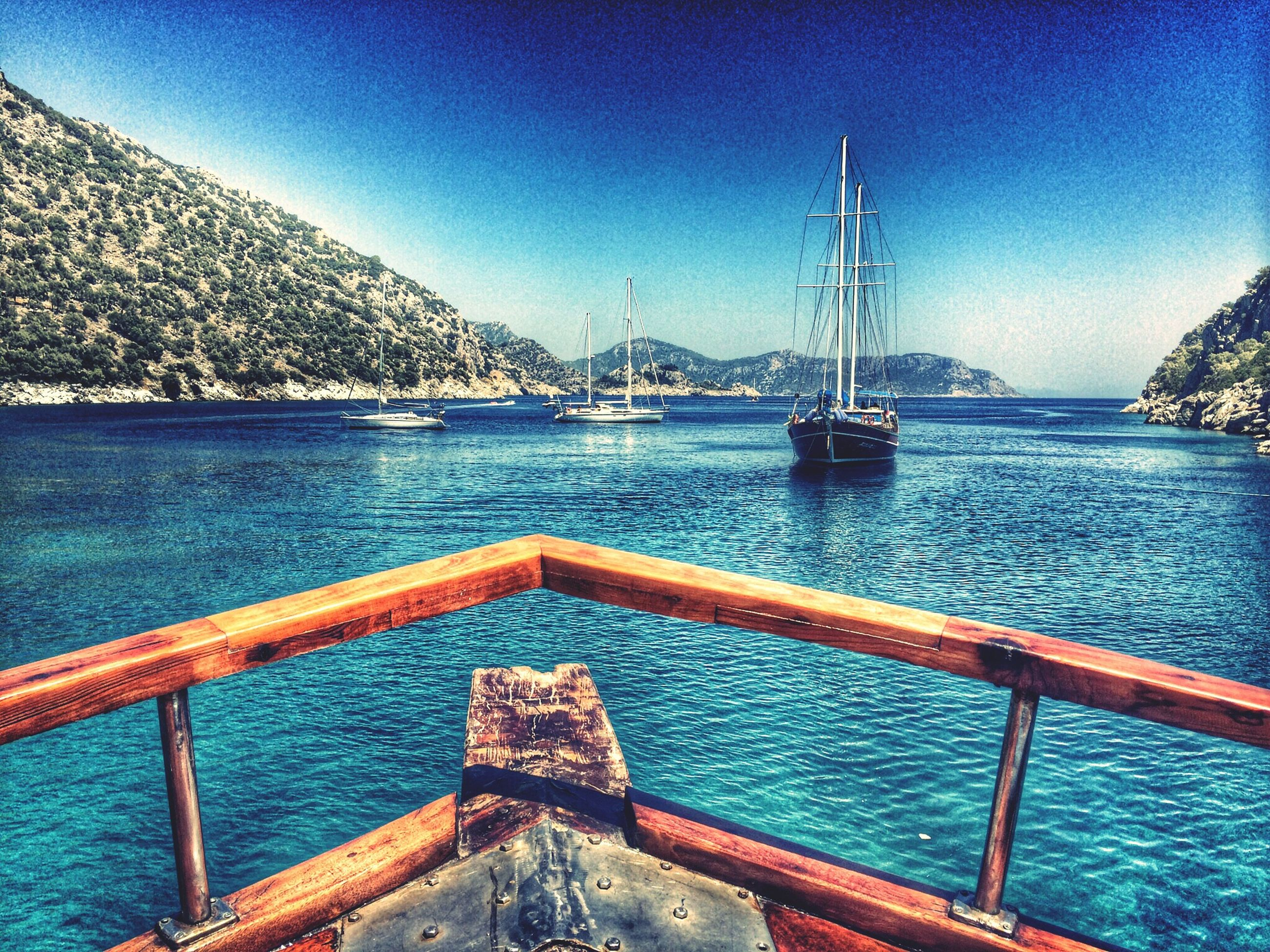 nautical vessel, transportation, water, mode of transport, boat, blue, sea, clear sky, moored, tranquility, mountain, tranquil scene, scenics, beauty in nature, nature, sailboat, pier, sailing, travel, sky