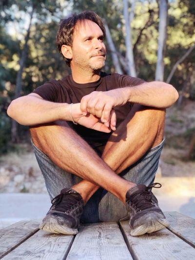 Full length of man sitting on wood