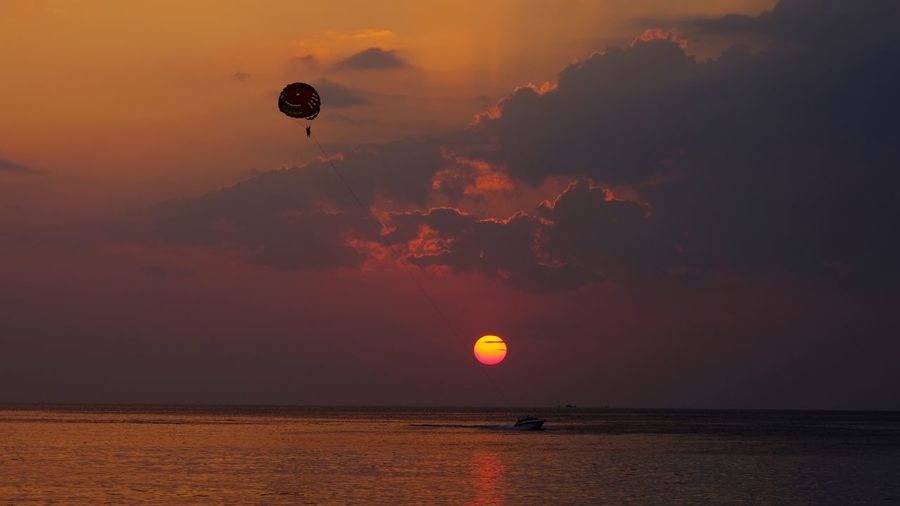 Holiday Reflection Beauty In Nature Evening Sky And Clouds Time Day Tourist Tourism Vacation Speed Boat Parasailing Sunset Sea Sky Beauty In Nature Nature Scenics Mid-air Sun Horizon Over Water Water Tranquil Scene Flying Adventure Outdoors Tranquility Silhouette Parachute Extreme Sports