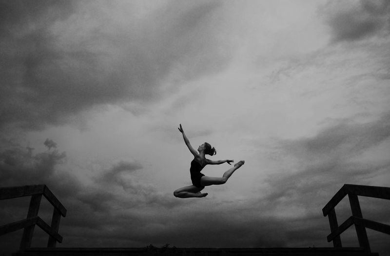 Low angle view of woman jumping against cloudy sky