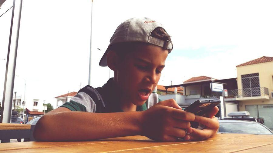 Boy using phone at table