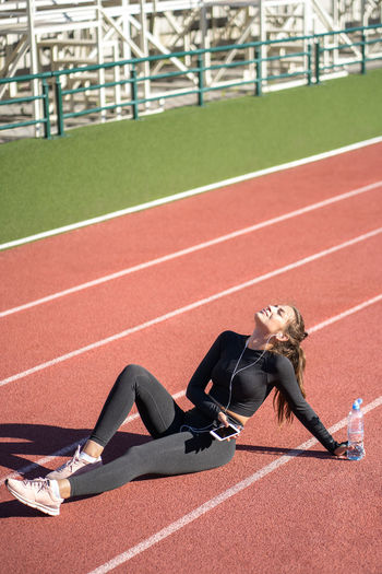 Full length of woman listening music while sitting on running track