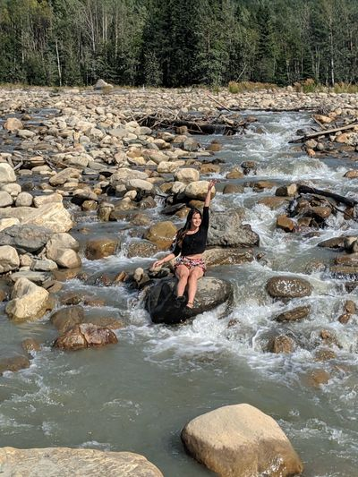 Portrait of woman sitting on rock by river