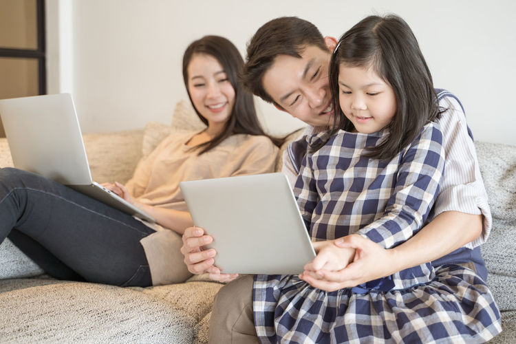 happy asian family spending time together on sofa in living room. family and home concept Asian  Family Happiness Happy Happy People Family Time Home House Daughter Parent Father Mother Dad Mom Love Lifestyles Living Room ASIA Japanese  Korean Thai Taiwan Smiling Smile Fun Portrait Girls Laptop Tablet