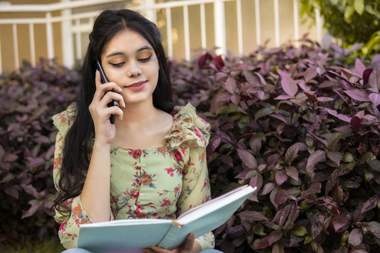 Young woman looking away while using mobile phone outdoors