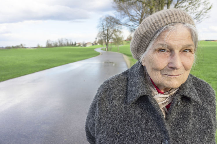 Portrait Of Senior Woman Standing On Road Against Field