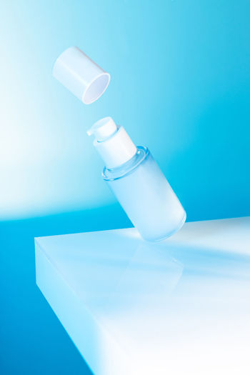 Close-up of bottle on table against blue background