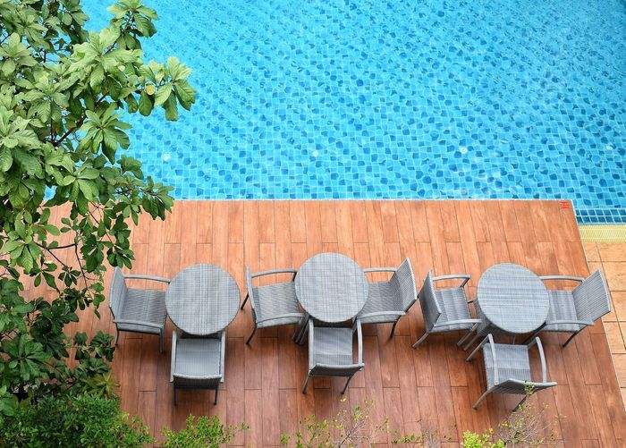 High angle view of chairs by swimming pool