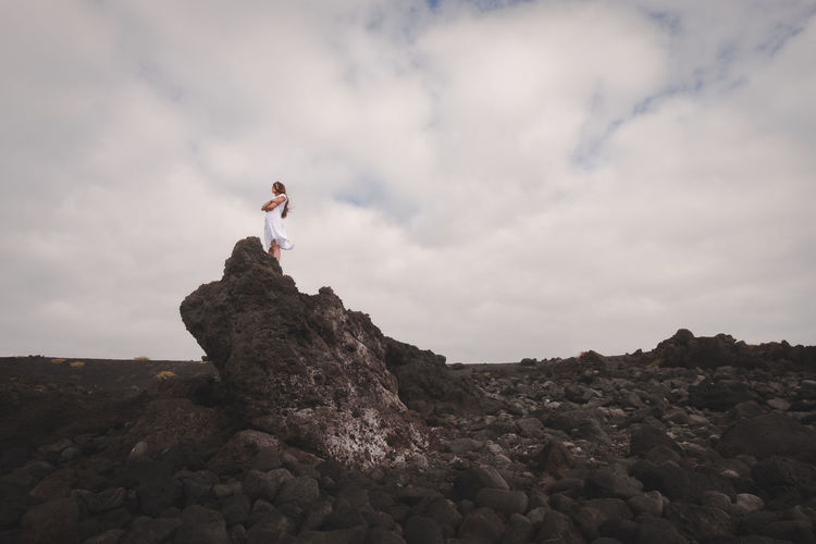 Low angle view of young man standing on rock against cloudy sky