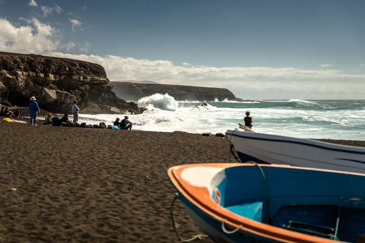 Panoramic view of dark sand beach against sky, fuerteventura