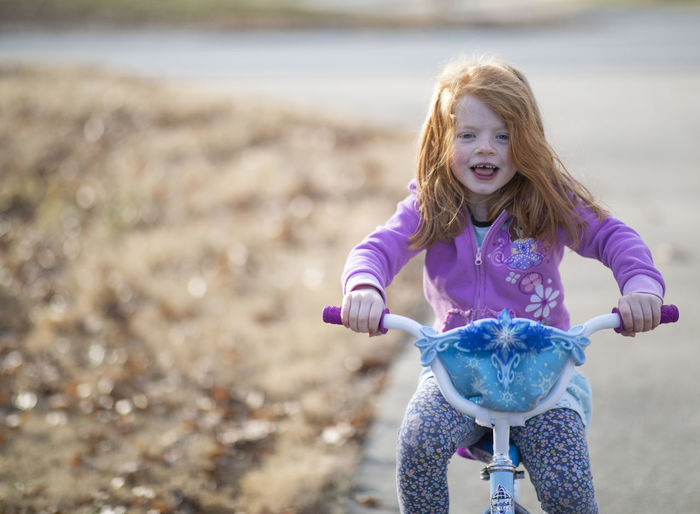 A five-year-old girl with red hair and blue eyes rides her bicycle on a warm winter day. Childhood Child Front View One Person Girls Leisure Activity Hair Land Casual Clothing Focus On Foreground Women Innocence Females Day Happiness Looking At Camera Emotion Holding Blond Hair Mouth Open Outdoors Hairstyle Bicycle Riding Bike Red Hair