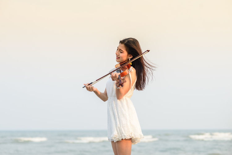 Portrait Of Young Woman Playing Violin At Beach Against Clear Sky