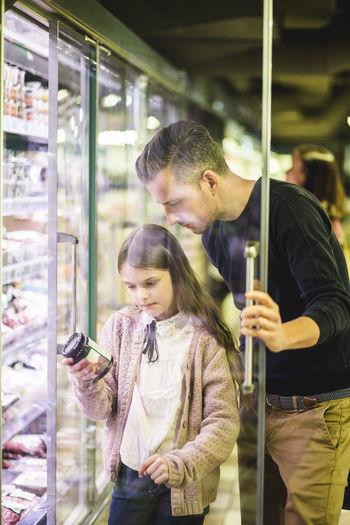 Man and woman using smart phone at store