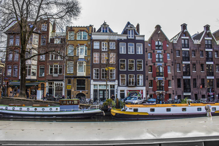 Amsterdam Amsterdam Architecture Architecture Bare Tree Building Building Exterior Built Structure City Day Luxury Mode Of Transportation Nature Nautical Vessel No People Outdoors Residential District River Row House Sky Transportation Tree Water Window