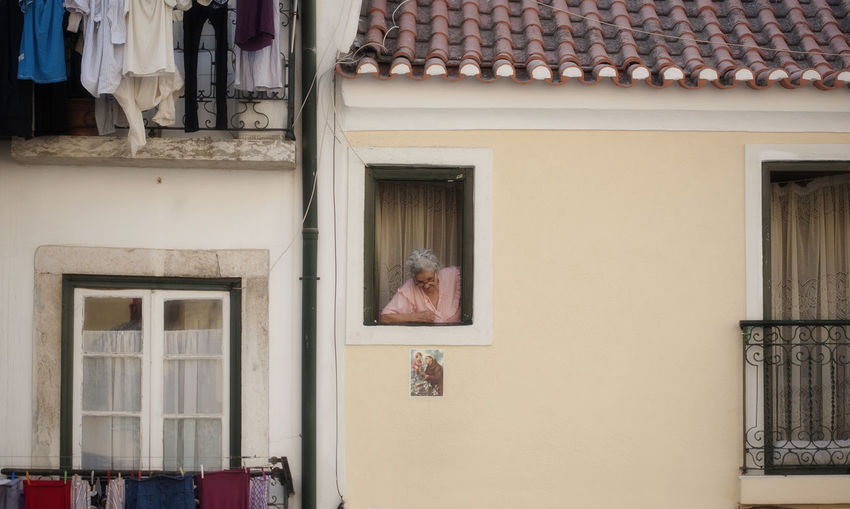 Architecture Building Exterior Built Structure Hanging Laundry House Residential Building Window Windows Woman In Window