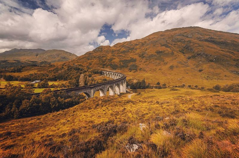 Bridge Over Field Against Cloudy Sky At Glenfinnan