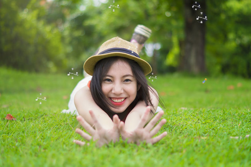Portrait of smiling teenage girl with arms raised lying on grassy field in park