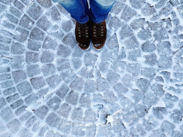 Low Section Of Person Standing On Snow Covered Cobblestone
