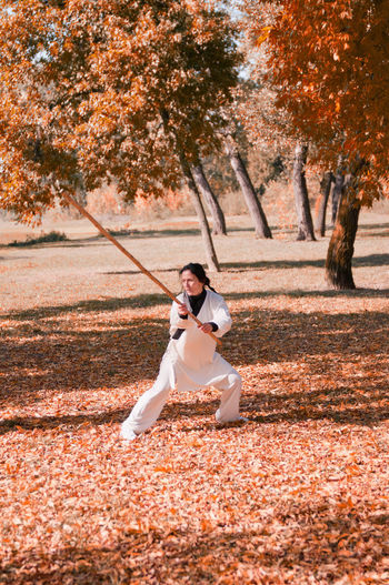 Woman practicing martial arts on autumn leaves