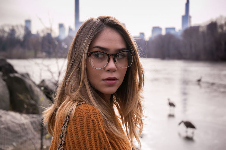 Close-up of beautiful woman with blond hair standing against lake
